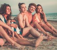 Amis ethniques multi détendant sur une plage Photos libres de droits