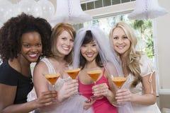 Amis ethniques multi heureux tenant des verres de cocktail Image stock