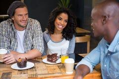 Amis ethniques multi parlant à la table dans le café Images libres de droits