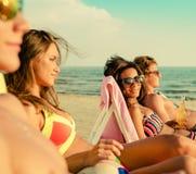 Amis ethniques multi prenant un bain de soleil sur une plage Image libre de droits