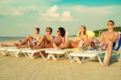 Amis ethniques multi prenant un bain de soleil sur une plage Photographie stock libre de droits