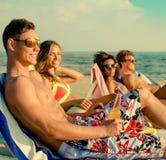 Amis ethniques multi prenant un bain de soleil sur une plage Photographie stock