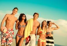 Amis ethniques multi prenant un bain de soleil sur une plage Images libres de droits