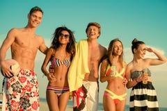 Amis ethniques multi prenant un bain de soleil sur une plage Images stock