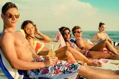Amis ethniques multi prenant un bain de soleil sur une plage Photo libre de droits