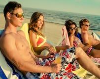 Amis ethniques multi prenant un bain de soleil sur une plage Photo stock