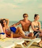 Amis ethniques multi prenant un bain de soleil sur une plage Photos stock