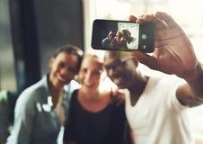 Amis ethniques multi prenant un selfie Photos stock