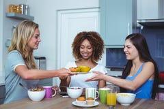 Amis ethniques multi tenant le plat avec la papaye dans la maison Photographie stock libre de droits