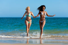 Amis exécutant des vacances de plage Photos stock