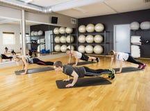 Amis exécutant l'exercice de planche dans le gymnase Image libre de droits