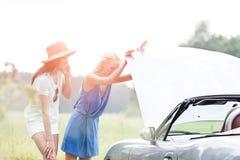Amis examinant la voiture décomposée le jour ensoleillé Photos libres de droits