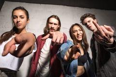 Amis fâchés de hippies se tenant au-dessus du fond gris images libres de droits