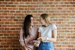 Amis féminins à l'aide d'un smartphone ensemble Images libres de droits