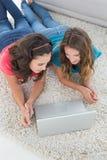 Amis féminins à l'aide de l'ordinateur portable à la maison Photo stock