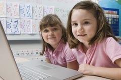 Amis féminins à l'aide de l'ordinateur portable Photos stock