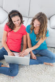 Amis féminins à l'aide de l'ordinateur portable dans le salon Photographie stock