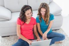Amis féminins à l'aide de l'ordinateur portable dans le salon Image libre de droits