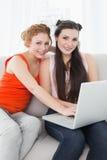 Amis féminins à l'aide de l'ordinateur portable ensemble à la maison Images stock