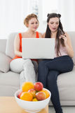 Amis féminins à l'aide de l'ordinateur portable ensemble à la maison Image libre de droits