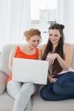 Amis féminins à l'aide de l'ordinateur portable ensemble à la maison Photographie stock