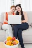 Amis féminins à l'aide de l'ordinateur portable ensemble à la maison Photographie stock libre de droits
