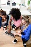 Amis féminins à l'aide de l'ordinateur portable tout en buvant du café Photo stock
