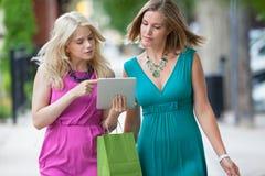 Amis féminins à l'aide de la Tablette de Digital Photo stock