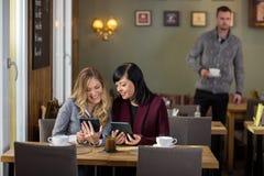 Amis féminins à l'aide des Tablettes de Digital au café Photo libre de droits