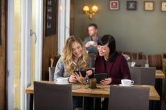 Amis féminins à l'aide des Tablettes de Digital au Tableau Image stock