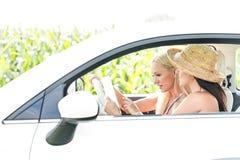 Amis féminins à l'aide du comprimé numérique dans la voiture Photographie stock