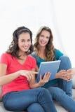Amis féminins à l'aide du comprimé numérique dans le salon Photo stock