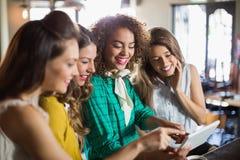 Amis féminins à l'aide du comprimé numérique en café Photos stock