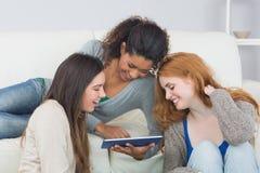 Amis féminins à l'aide du comprimé numérique ensemble à la maison Image libre de droits