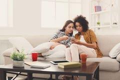 Amis féminins à l'aide du smartphone à la maison Images stock