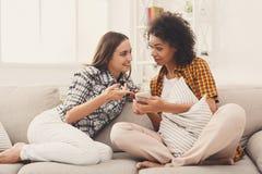 Amis féminins à l'aide du smartphone à la maison Photographie stock libre de droits