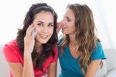 Amis féminins à l'aide du téléphone portable à la maison Images libres de droits