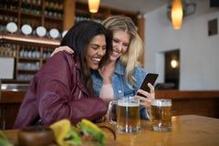 Amis féminins à l'aide du téléphone portable dans la barre Photos libres de droits