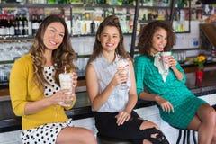 Amis féminins à la mode ayant la boisson dans le restaurant Photographie stock
