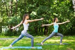 Amis féminins établissant et faisant le yoga dehors Image libre de droits
