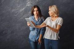Amis féminins étonnés à l'aide du comprimé au fond foncé de studio Photographie stock