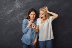 Amis féminins étonnés à l'aide du smartphone au fond foncé de studio Photo libre de droits