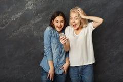 Amis féminins étonnés à l'aide du smartphone au fond foncé de studio Photos libres de droits