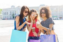 Amis féminins étonnés avec le smartphone dehors Photo stock