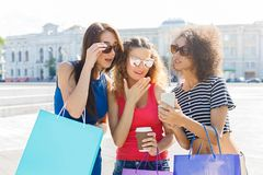 Amis féminins étonnés avec le smartphone dehors Photographie stock