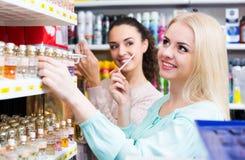 Amis féminins achetant le parfum Photos stock