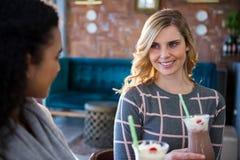 Amis féminins agissant l'un sur l'autre les uns avec les autres tout en ayant le café Images stock