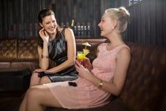 Amis féminins agissant l'un sur l'autre les uns avec les autres tout en ayant le cocktail Photos stock