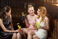Amis féminins agissant l'un sur l'autre les uns avec les autres tout en ayant le cocktail Photo stock