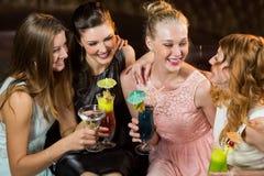 Amis féminins agissant l'un sur l'autre les uns avec les autres tout en ayant le cocktail Photographie stock